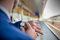 Rear view of businessman looking at his watch while waiting in train station