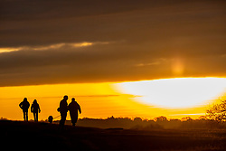 © Licensed to London News Pictures. 03/12/2019. London, UK. Dog walkers enjoy a spectacular sun rise in Richmond Park as weather forecasters predict frosty starts and freezing fog for the South East. Photo credit: Alex Lentati/LNP