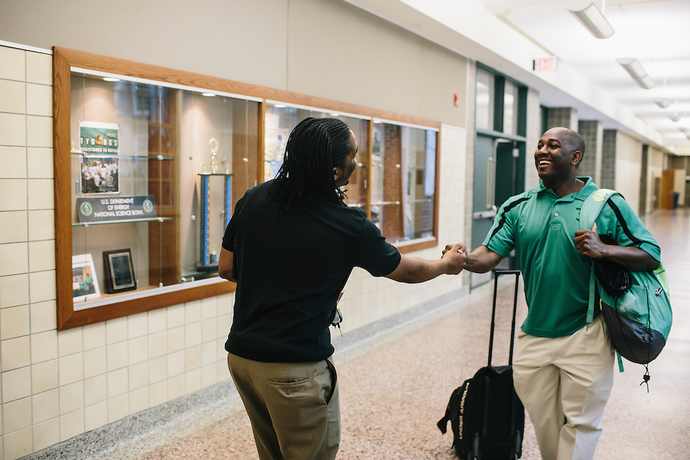 Marc Davis greets track and field coach Desmond Dunham, right, at Woodrow Wilson High School in Washington DC. Davis, once worried his career path would be on the streets, mixed up with drug dealers, but after being mentored by UDC professor Dr. Daryao Khatri, Davis, only 23, is now an algebra and geometry teacher.