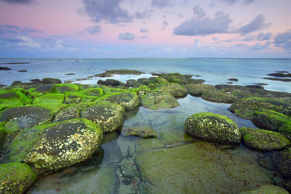 The beautifully encrusted rocks clustered together on the shores of Bulcock Beach make a captivating foreground for this photograph.
