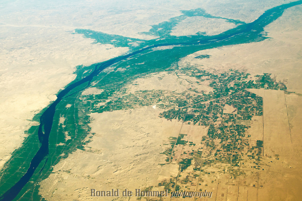 The Nile valley in central Egypt seen from the air. A bright green strip of fertile land is surrounded by dry desert.