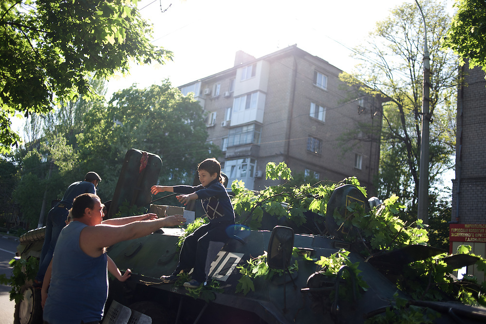 Pro-Russian activists inspect an armoured personal carrier left behind by the Ukrainian army the day before due to a faulty engine as fighting between Ukrainian troops and armed separatist groups erupted.