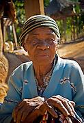 Village elder sits around during the mid-afternoon heat.