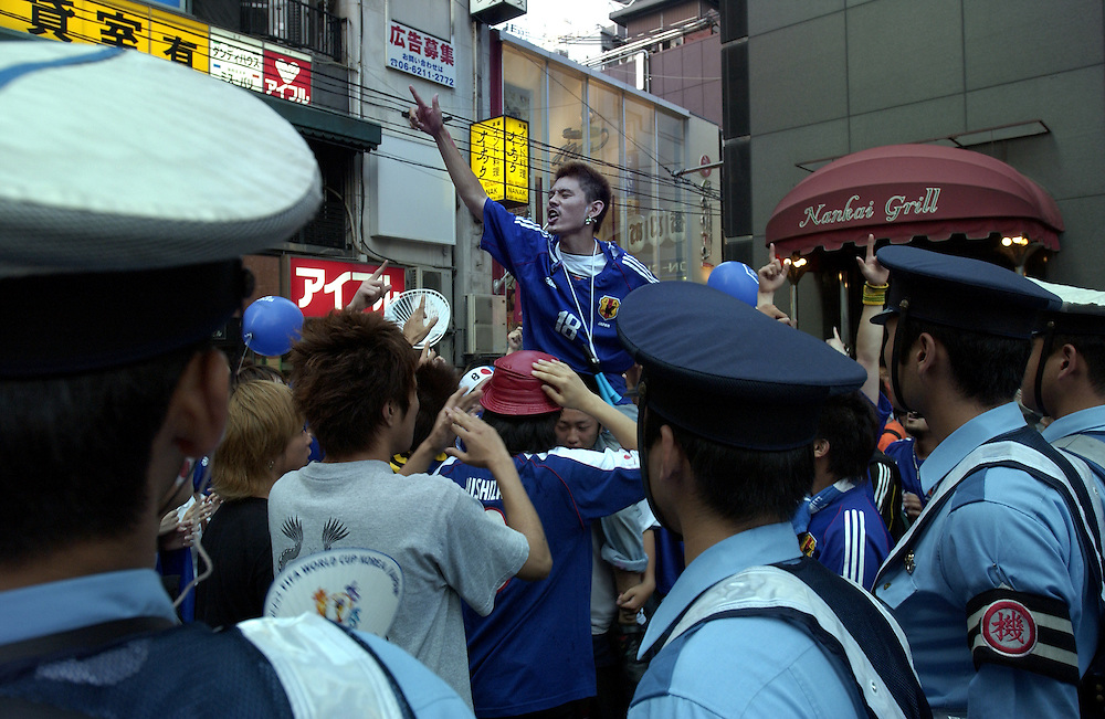 Japanese football supporters cheer their team's efforts despite Japan's loss to Turkey. Minami area, Osaka Japan.18/06/02..©David Dare Parker/AsiaWorks Photography