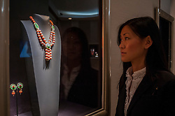 © Licensed to London News Pictures. 24/06/2015. London, UK.   A gallery staff member looks at an ornate necklace by Van Cleef and Arpels, at the preview of Masterpiece London, the international cross-collecting Fair for art, antiques and design which takes place at The Royal Hospital Chelsea 25 June to 1 July. Photo credit : Stephen Chung/LNP