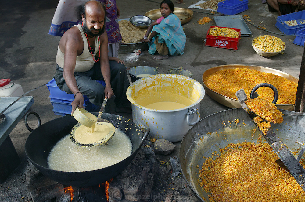 Preparing boondi in Ujjain, India, at one of the camps at the Kumbh Mela site. Every camp had its own large/small kitchen where food is prepared for people residing in that particular camp as well as outsiders who would walk in and out for lunch/dinner. Boondi can be a savory preparation or even sweet. A thin, consistency dough is prepared using gram flour, water and spices. The man is pouring this dough through a big iron sieve which has holes in it so the dough falls in the form of drops in the hot oil and this is then fried. What comes out is the savory boondi. This boondi can be made sweet by putting in sugar syrup (prepared separately). (Supporting image from the project Hungry Planet: What the World Eats)..