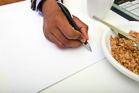 Close up of Indian mans hands writing on paper next to cereal