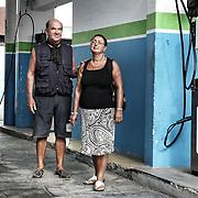 """Gesti quotidiani di risparmio energetico.<br /> Energy efficiency opportunities act. <br /> <br /> Progetto per immagini e parole """"Colti in flagranza di risparmio energetico"""" dei fotografi Michele D'Ottavio e Ornella Orlandini.<br /> <br /> LINO e ANGELA, 63 e 60 anni, pensionati<br /> ore 10.20<br /> <br /> Torino - corso Botticelli Colti nell'atto di rifornirsi di metano.<br /> <br /> Ho sempre usato l'auto aziendale per spostarmi. Quando mi sono comprato la mia macchina ho deciso di prenderla a metano per inquinare il meno possibile. Non prendo i mezzi perché sono scomodi per gli spostamenti che devo fare. L'auto è un mezzo di trasporto, per me ha solo questo uso. Dicono che non sia potente o che non vada veloce, io la uso in città e in autostrada. Spendo la metà di prima. Costa un po' di più all'acquisto, un 15-20% in più di una a benzina, ma non mi interessa perché non inquina. Sono pochi i distributori di metano, ma esiste una guida per sapere in ogni zona d'Italia dove ti puoi rifornire. Il serbatoio ha un'autonomia di 260 km e non sono mai rimasto a piedi, in casi estremi puoi fare benzina: l'iniezione funziona ancora così. Quando vado a rifornirmi, devo avere le monete. Il pieno è circa 8 euro."""