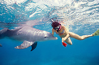 Female snorkler playing with wild dolphin.
