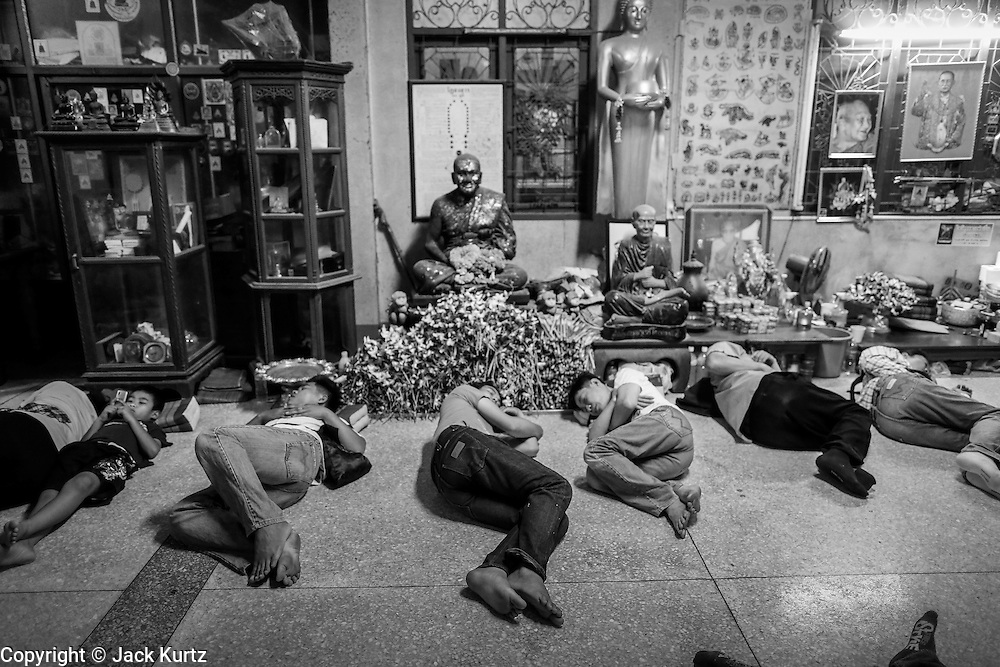 "14 MARCH 2014 - NAKHON CHAI SI, NAKHON PATHOM, THAILAND: People sleep on the floor in the temple during the tattoo festival at Wat Bang Phra. Wat Bang Phra is the best known ""Sak Yant"" tattoo temple in Thailand. It's located in Nakhon Pathom province, about 40 miles from Bangkok. The tattoos are given with hollow stainless steel needles and are thought to possess magical powers of protection. The tattoos, which are given by Buddhist monks, are popular with soldiers, policeman and gangsters, people who generally live in harm's way. The tattoo must be activated to remain powerful and the annual Wai Khru Ceremony (tattoo festival) at the temple draws thousands of devotees who come to the temple to activate or renew the tattoos. People go into trance like states and then assume the personality of their tattoo, so people with tiger tattoos assume the personality of a tiger, people with monkey tattoos take on the personality of a monkey and so on. In recent years the tattoo festival has become popular with tourists who make the trip to Nakorn Pathom province to see a side of ""exotic"" Thailand.   PHOTO BY JACK KURTZ"