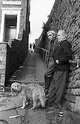 With the companionship of a pet dog, an elderly gentleman reminisces about the good old days with a life-long buddy at Alexandra Terrace, in the south Wales town of Abertillery (Welsh: Abertyleri). Together they lean against a stone wall of a road above and look down the hill of their street they may have lived all their lives. In the distance, a younger generation of young girls play at the far end. The men might once have been working men, old coal miners like many folk in this community whose  population rose steeply during the period of (now defunct) mining development in South Wales, being 10,846 in 1891 and 21,945 ten years later. Lying in the mountainous mining district of the former counties of Monmouthshire and Glamorganshire, in the valley of the Ebbw Fach..