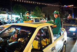 © Licensed to London News Pictures. 27/04/2014. Sulaimaniya, Iraq. Two girls, wearing hats, T-shirts and scarves of the Patriotic Union of Kurdistan (PUK) political party, hang out of the windows of a taxi during celebrations in the lead up to the 2014 Iraqi parliamentary elections in Sulaimaniya, Iraqi-Kurdistan.<br /> <br /> Although banned in other parts of Iraqi-Kurdistan, the days leading up to an election in Sulaimaniya sees political supporters of all the three main parties parading up and down the main street of the city, waving flags, honking horns, letting off fireworks and firing pistols and rifles into the air.<br /> <br /> The period leading up to the elections, the fourth held since the 2003 coalition forces invasion, has already seen six polling stations in central Iraq hit by suicide bombers causing at least 27 deaths. Photo credit: Matt Cetti-Roberts/LNP