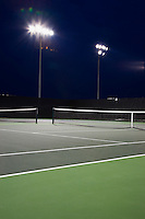 Outdoor tennis court illuminated at night