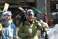 Two women skiers laugh as they walk through Whistler Village on a sunny winter day while carrying a coffee.