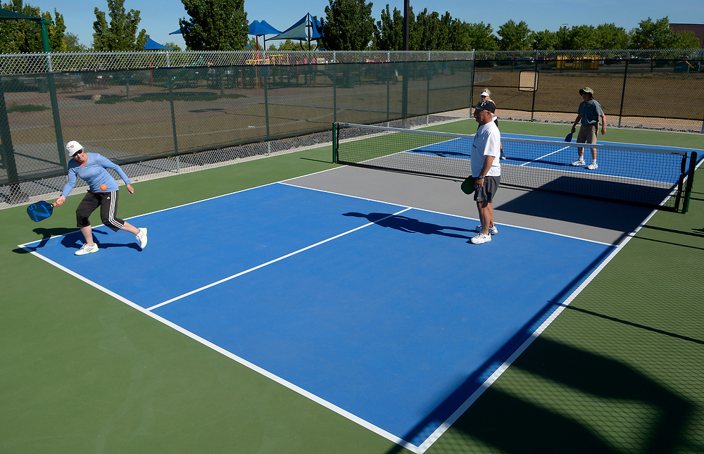 gbs052417a/ASEC -- Sandy Salm reaches for the ball as she plays pickle ball with Mike Adams, Jenny Adams and her husband Lou Salm, from left, on Wednesday, May 24, 2017. They play on the new 24 pickle ball court complex at Manzano Mesa Park. The courts include six championship tournament courts with energy-efficient LED lighting and spectator seating. Mike Adams, a member of the ABQ Pickleball Club, said the National Senior Pickleball Games will be played on the courts in 2019.(Greg Sorber/Albuquerque Journal)