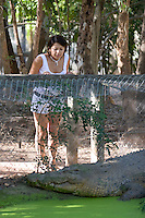 A woman gets up close and personal with a giant Estuarine (Saltwater) Crocodile at Townsville's Billabong Sanctuary.