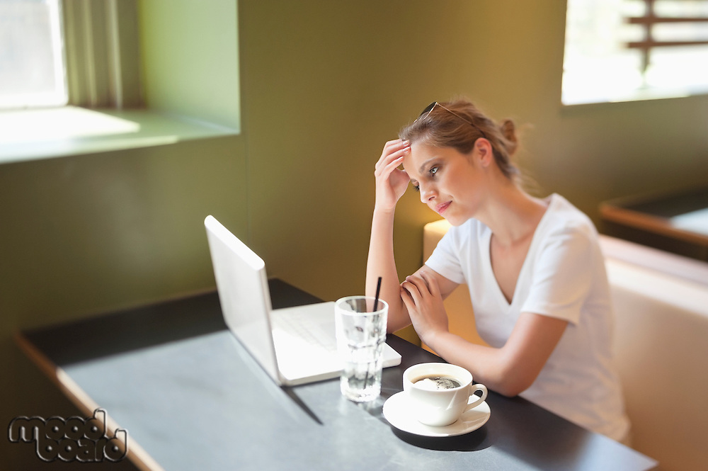 Young woman working on laptop at cafe