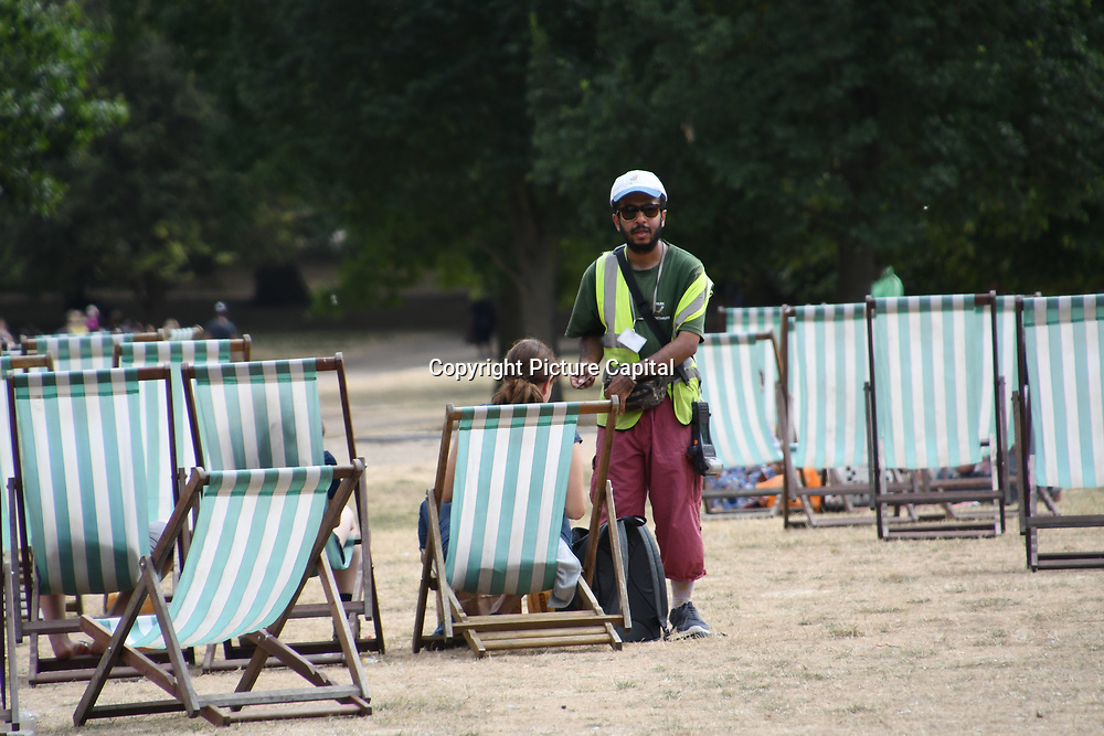 Deckchairs man collecting monies from people sitting at Green Park as Heatwaves continues in the UK on July 22 2018,  London, UK