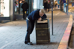 "© Licensed to London News Pictures. 19/12/2014. Brighton, UK. A man using a bin as support after getting drunk while going out on ""Mad Friday"" night in Brighton East Sussex (19/12/2014). Across the UK thousands of people begin 2 weeks of festivities over the Christmas Period. Photo credit : Hugo Michiels/LNP"