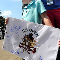 A young fan looks hopefully from players at the final round of the U.S. Open golf championship to sign his flag at Oakmont Country Club near Pittsburgh, on June 19, 2016.  Photo by Archie Carpenter/UPI
