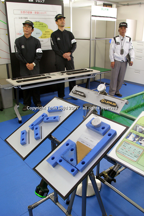 "This is a demonstration of the training studio or martial arts style ""dojo"" at Toyota Motor Corp.'s Tahara plant in Aichi Prefecture. Here Lexus workers are trained to detect the smallest flaws and defects that robots and computers can't detect. Something like a martial arts class, this training is where workers are taught mental skills like how to gauge bolt tightening or how to insert parts on the line just right. They are also ranked by their skill level and are tested every four months for technique. These skill levels include: Master Craftsmen, Assistant Master Craftsmen, and Craftsmen. According to Toyota management, workers are trained for body and mind which is reflected in the quality of their product. Some of the training includes finger exercises with specially designed rubber nets, the arranging of colors patterns, and feeling tests while wearing cotton gloves. This is in addition to the classrooms training where workers are drilled on the concept of perfection. Besides the Lexus LS, GS and IS sedans manufactured here (hybrids included), Toyota also makes the Land Cruiser Prado, 4 Runner and RAV4 sport vehicles."