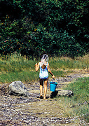 Young girl with bucket and net walking along a beach path, Orleans, Cape Cof, Massachusetts, USA