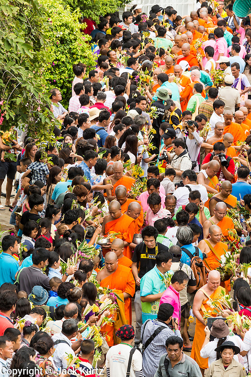 "22 JULY 2013 - PHRA PHUTTHABAT, THAILAND: Buddhist monks walk through the crowd before climbing the stairway to the Mondop (chapel that houses the footprint) before the Tak Bat Dok Mai at Wat Phra Phutthabat in Saraburi province of Thailand, Monday, July 22. Wat Phra Phutthabat is famous for the way it marks the beginning of Vassa, the three-month annual retreat observed by Theravada monks and nuns. The temple is highly revered in Thailand because it houses a footstep of the Buddha. On the first day of Vassa (or Buddhist Lent) people come to the temple to ""make merit"" and present the monks there with dancing lady ginger flowers, which only bloom in the weeks leading up Vassa. They also present monks with candles and wash their feet. During Vassa, monks and nuns remain inside monasteries and temple grounds, devoting their time to intensive meditation and study. Laypeople support the monastic sangha by bringing food, candles and other offerings to temples. Laypeople also often observe Vassa by giving up something, such as smoking or eating meat. For this reason, westerners sometimes call Vassa the ""Buddhist Lent.""       PHOTO BY JACK KURTZ"