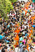 """22 JULY 2013 - PHRA PHUTTHABAT, THAILAND: Buddhist monks walk through the crowd before climbing the stairway to the Mondop (chapel that houses the footprint) before the Tak Bat Dok Mai at Wat Phra Phutthabat in Saraburi province of Thailand, Monday, July 22. Wat Phra Phutthabat is famous for the way it marks the beginning of Vassa, the three-month annual retreat observed by Theravada monks and nuns. The temple is highly revered in Thailand because it houses a footstep of the Buddha. On the first day of Vassa (or Buddhist Lent) people come to the temple to """"make merit"""" and present the monks there with dancing lady ginger flowers, which only bloom in the weeks leading up Vassa. They also present monks with candles and wash their feet. During Vassa, monks and nuns remain inside monasteries and temple grounds, devoting their time to intensive meditation and study. Laypeople support the monastic sangha by bringing food, candles and other offerings to temples. Laypeople also often observe Vassa by giving up something, such as smoking or eating meat. For this reason, westerners sometimes call Vassa the """"Buddhist Lent.""""       PHOTO BY JACK KURTZ"""