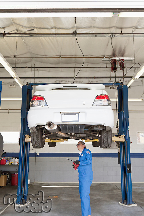 Mechanic checking underneath car on a lift
