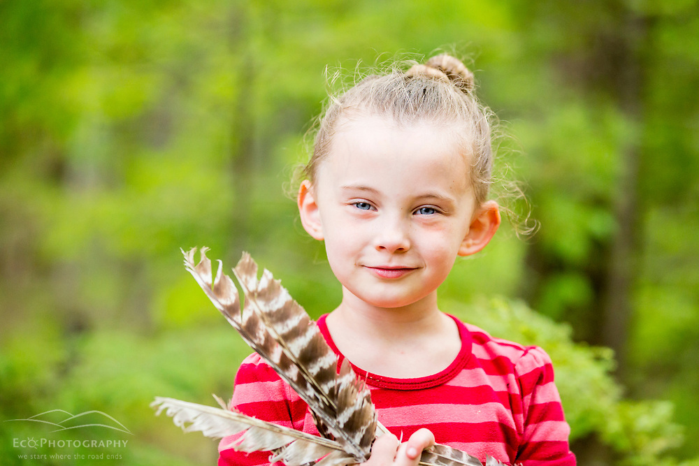 A young girl plays with turkey feathers in the woods at the Orris Falls Preserve in South Berwick, Maine.