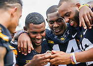 Iowa Hawkeye defensive players Miles Taylor, Desmond King and Anthony Gair look at a phone while waiting to have their photos taken at Media Day at the Kenyon Practice Stadium in Iowa City on Saturday, August 6, 2016. (Rebecca F. Miller/The Gazette)