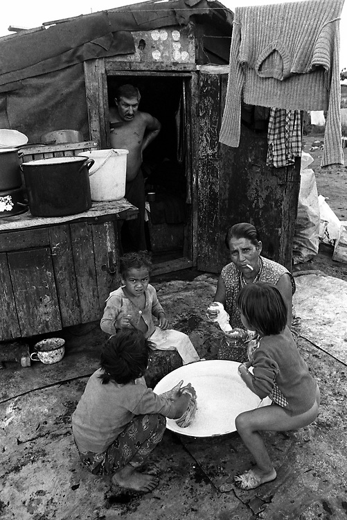 Title: The constant challenge of daily life in the illegally erected shacks at Pata-Rât Transylvania, Romania. August 1996..Morning family wash. Roma (Gyspy) family at Pata-Rat, a community of around 150 Roma living in make-shift shacks adjoining the rubbish dump on the outskirts of the city of Cluj-Napoca, Transylvania Romania. August 1996