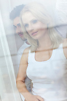 Beautiful young woman with man looking through hotel window