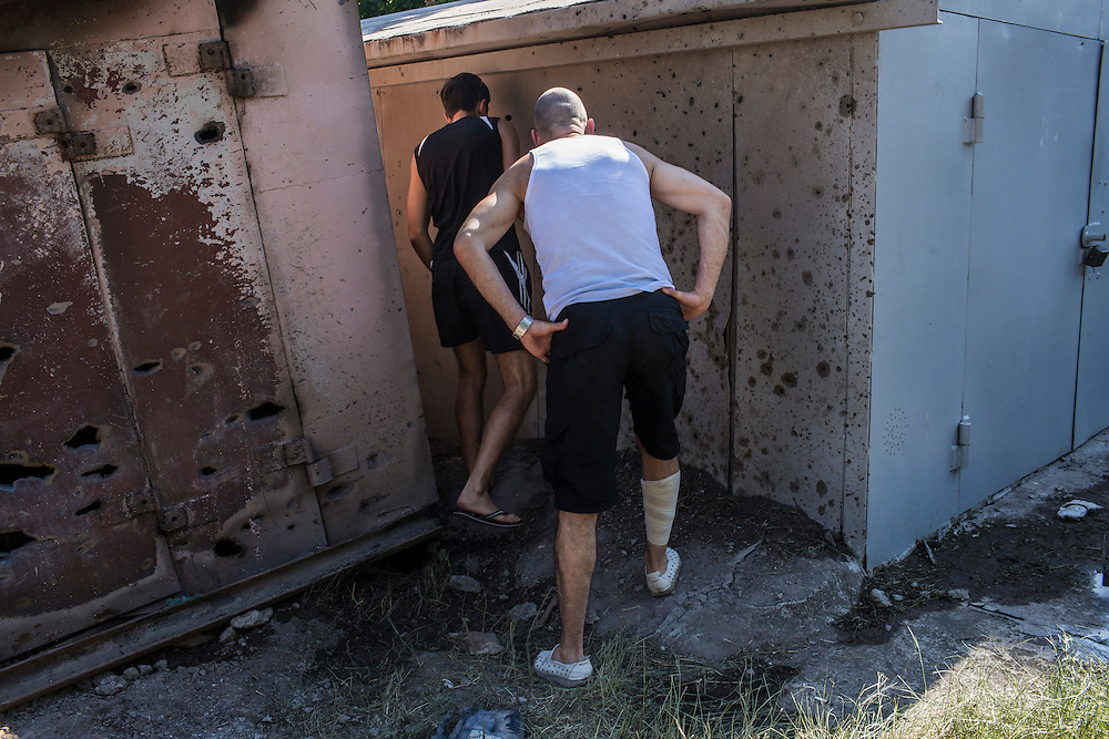 Local residents look at a destroyed garage after it was hit by a suspected grad rocket strike on Tuesday, July 29, 2014 in Donetsk, Ukraine.