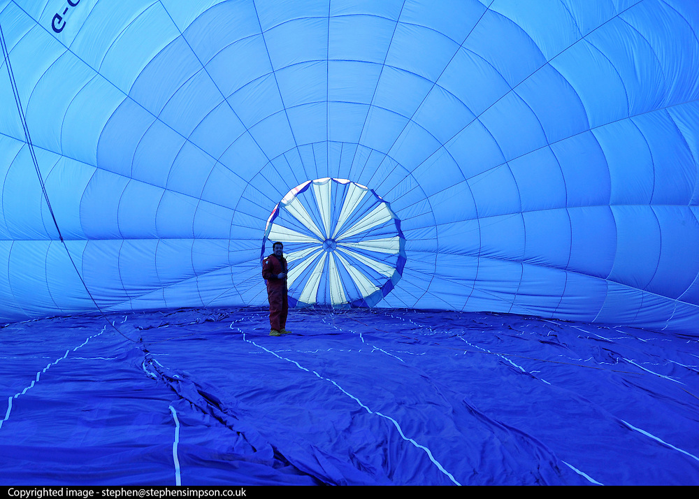 London News pictures. 07/04/2011. CANTERBURY: A flyer checks the inside of his balloon. Approximately 50 hot air balloons from across the UK and Europe take advantage of the weather window and take off from Lydden Hill Race Circuit, Wootton, Kent, to fly across the English Channel marking the largest ever group of balloons to attempt the crossing. The participants  have been waiting since October for the event to happen. Picture credit should read Stephen Simpson/LNP