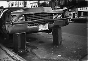 Cadillac propped up by wooden crates,Harlem, New York 1980