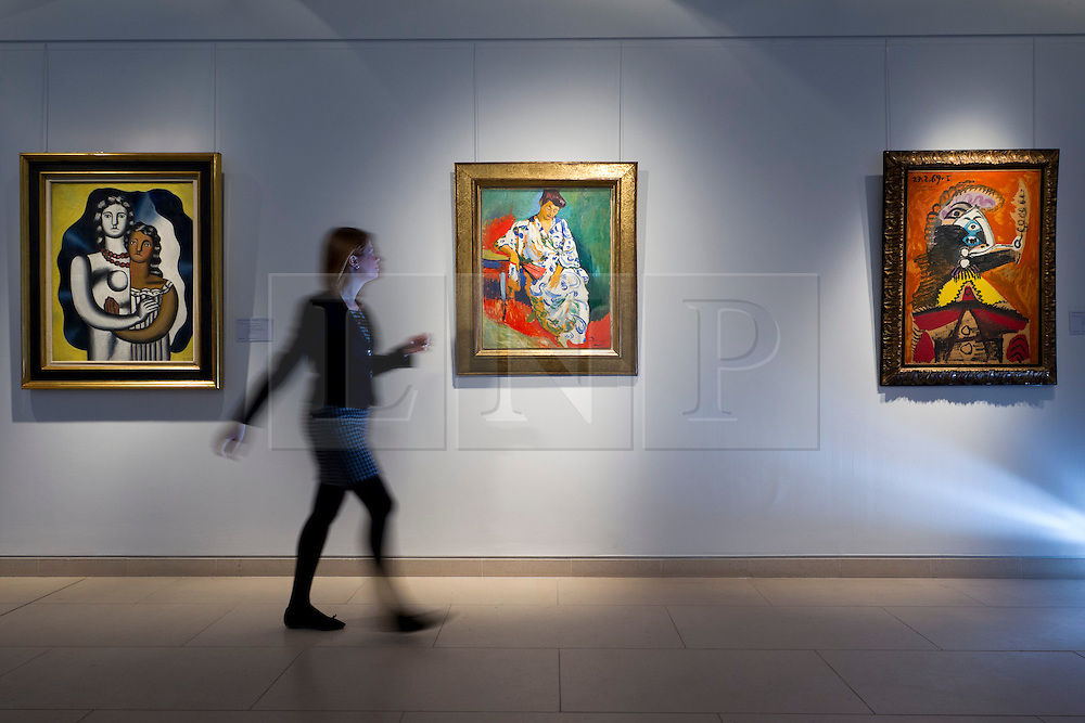 © Licensed to London News Pictures. 04/04/2013. London, UK. A Christie's employee walks past paintings including Andre Derain's 1905 portrait of the wife of Henri Matisse entitled 'Madame Matisse au kimono' (est. US$15,000,000-20,000,000) (C); Fernand Leger's 'Les deux figures' (1929, est. US$3,000,000-5,000,000) (L); and Pablo Picasso's 'Buste d'homme a la pipe' (1969, est US$900,000-1,200,000) at an auction press preview in St James, London, today (04/04/2013). The sale, consisting of Impressionist & Modern Art, is set to take place  on the 8th of May in Christie's New York premises.  Photo credit: Matt Cetti-Roberts/LNP