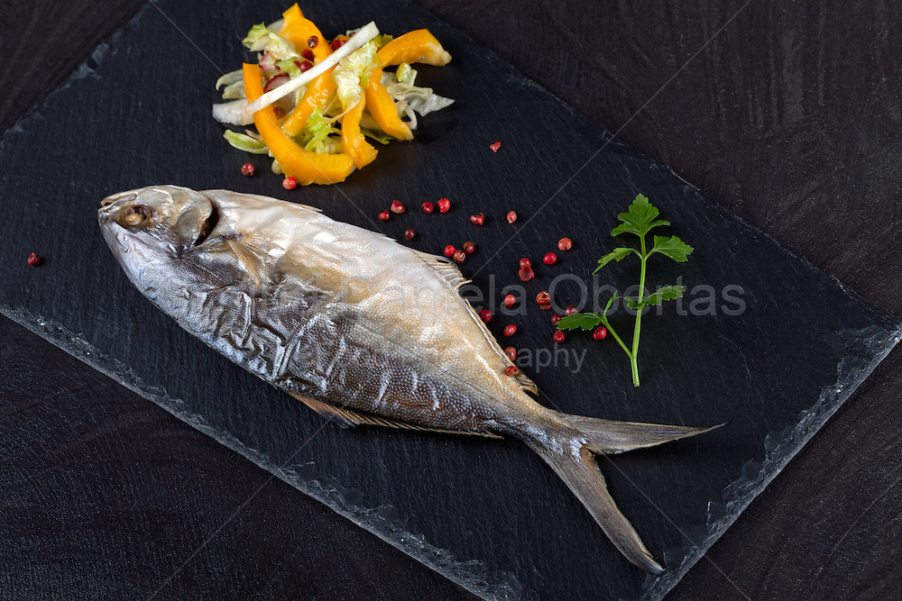Baked trevally fish garnished with mixed vegetables salad, peppercorns and parsley, on black stone plate.