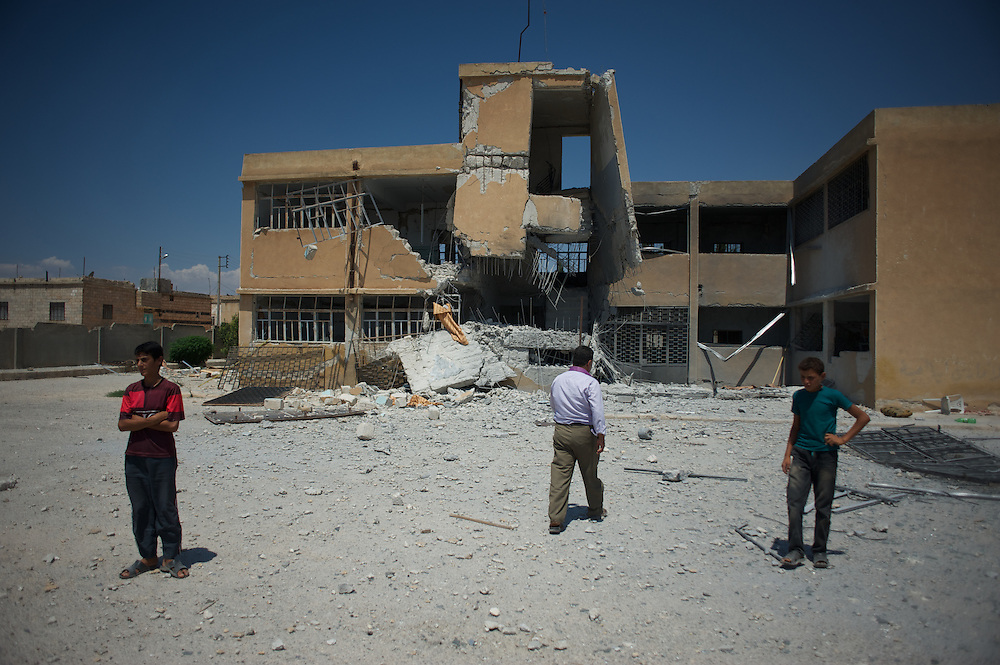 August 11, 2012 - Tarafat, Aleppo, Syria: Local residents pass by the  destroyed Jamal-Jamal school in Tarafat village, near Aleppo. The Syrian Army warplanes have recently bombed residential areas and the only two schools in the village, with 200 kilogram bombs. (Paulo Nunes dos Santos/Polaris)