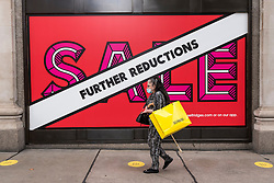 © Licensed to London News Pictures. 28/07/2020. LONDON, UK. A shopper outside Selfridges' flagship store on Oxford Street.  Selfridges has announced that staff numbers will be reduced by 450 (14% of the total headcount) as annual sales are expected to be significantly less than the prior year.  The coronavirus pandemic and general downturn in the retail industry are cited  as the main reasons for the job cuts..  Photo credit: Stephen Chung/LNP