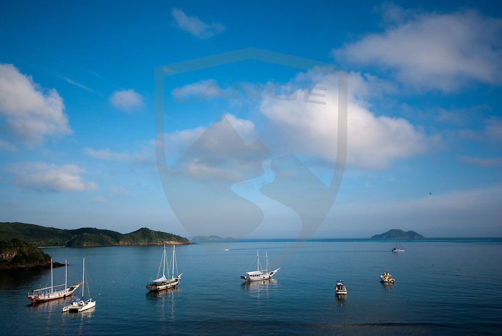 the ocean landscape marina of buzios, rio de janeiro, brazil with cloud filled blue sky and boats along the shore.  horizontal composition.