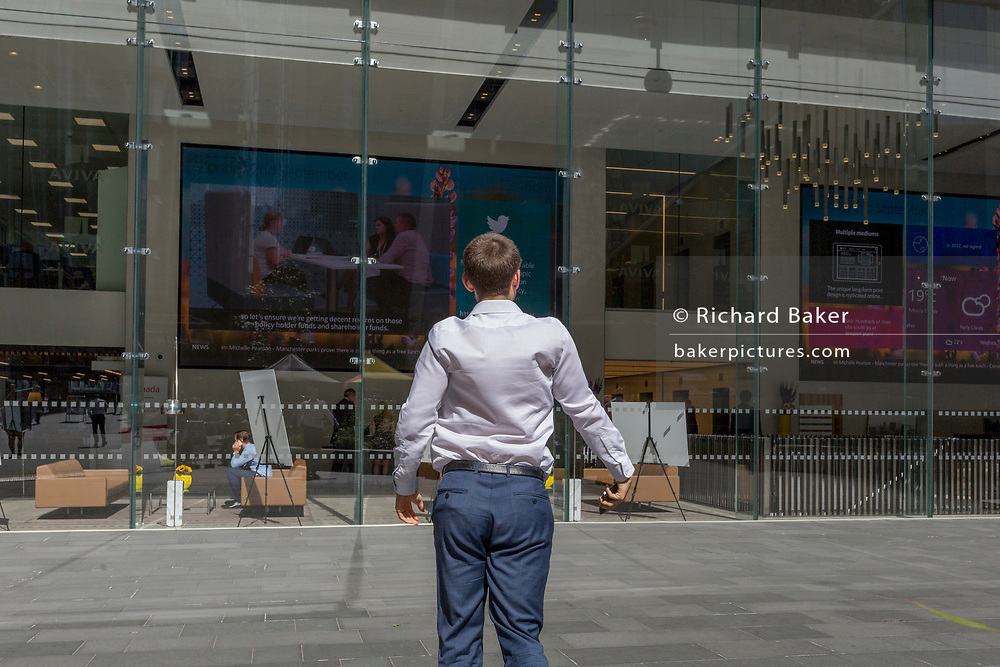 A young (able-bodied, not disabled) businessman stretches after eating lunch at leadenhall in the City of London, (aka The Square Mile) the capital's financial district, on 2nd September 2019, in London, England.