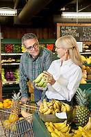 Senior woman with banana while mature man looking in farmer's market