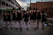 Students of the Manguinhos community ballet dance together as they walk through their community  in Manguinhos neighbourhood, Rio de Janeiro, Brazil, Monday, June 11, 2018. The Manguinhos community ballet has been a reprieve from the violence and poverty that afflicts its namesake neighborhood for hundreds of girls who have benefitted from free dance classes since 2012. (Dado Galdieri for The New York Times)