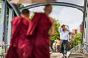 12 JUNE 2013 - YANGON, MYANMAR: A man walks past Buddhist monks on his way to a boat landing on the Irrawaddy River in Yangon, Myanmar.         PHOTO BY JACK KURTZ