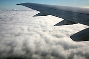 Aeroplane wing of plane cruising in blue sky high above clouds over Europe