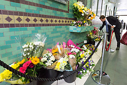 © Licensed to London News Pictures. 07/07/2015. London, UK. A man lays flower shortly before people observe a minute silence at Aldgate tube station in London, on the tenth anniversary, for victims of the 7/7 bombings. Photo credit : Vickie Flores/LNP