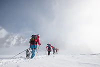 A close-up low-angle perspective on a team of four mountaineers as seen druing a long and exhausting traverse of Glacier Blanche on a cold and cloudy Winter day.