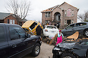 A family gathers outside of a home that was hit by a tornado two days earlier in Garland, Texas on December 28, 2015. (Cooper Neill for The New York Times)
