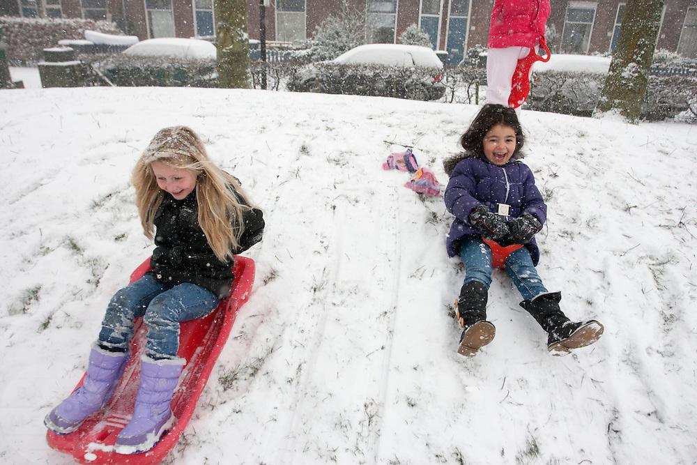 Kinderen glijden in de Utrechtse wijk Ondiep van een heuveltje in de speeltuin.<br /> <br /> Children are playing in the snow.